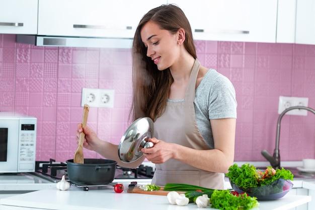 Kobieta w fartuch gotowania obiad ze świeżych dojrzałych warzyw w domu w kuchni