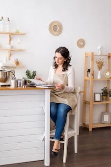 Kobieta w fartuchu czyta książkę kucharską. przygotowanie do gotowania