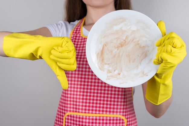 Kobieta w fartuchu i gumowych rękawiczkach popycha brudny talerz i palec w dół
