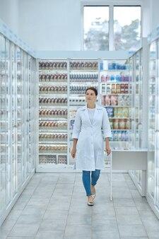 Kobieta w fartuchu laboratoryjnym między półkami z lekami