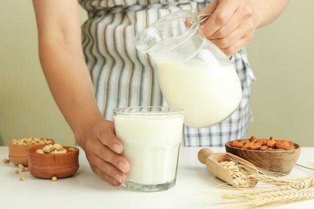 Kobieta w fartuchu nalewa mleko do szklanki