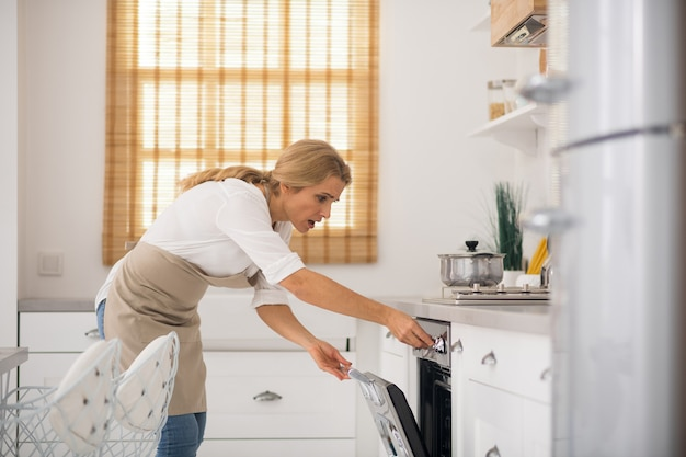 Kobieta w fartuchu, otwierając piekarnik w kuchni