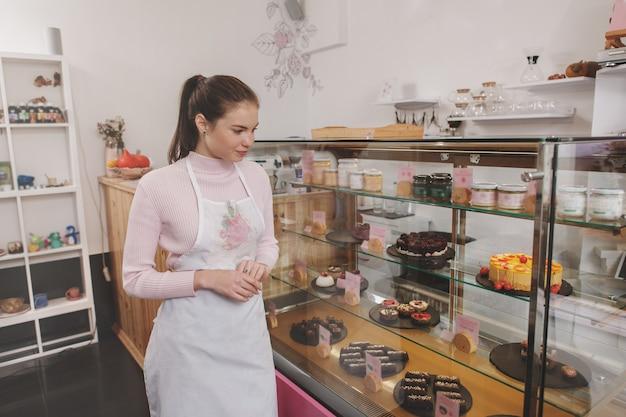 Kobieta w fartuchu, pracująca w swojej kawiarni z wegańskimi deserami