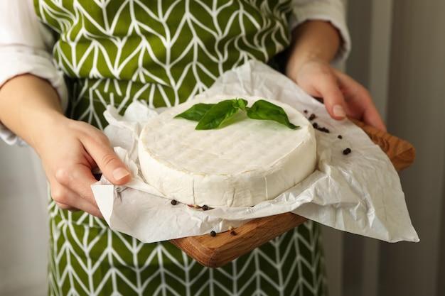 Kobieta w fartuchu trzymać deskę do krojenia z camembertem