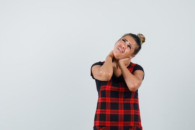 Kobieta w fartuszku cierpiąca na ból szyi i wyglądająca na zmęczoną, widok z przodu.
