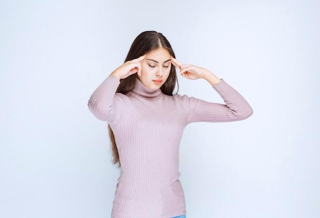 Kobieta w fioletowej koszuli myśli i analizuje.