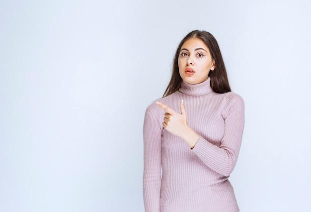 Kobieta w fioletowej koszuli pokazując coś po lewej stronie.