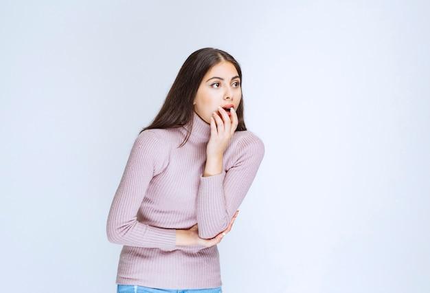 Kobieta w fioletowej koszuli wygląda na zaskoczoną i zamyśloną.