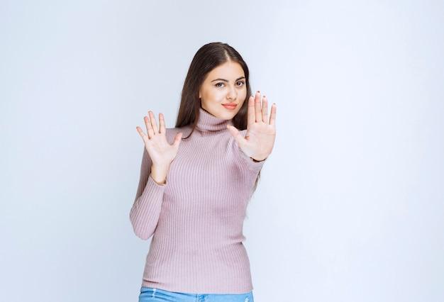 Kobieta w fioletowej koszuli zatrzymując coś rękami.