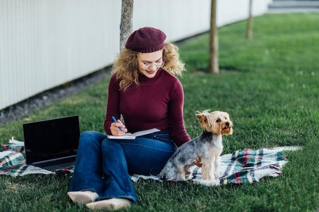 Kobieta w fioletowym kapeluszu na pikniku w lesie, obok niej na kocu mały piesek yorkshire terrier. światło słoneczne, jasne nasycenie kolorów, jedność z naturą i zwierzętami.