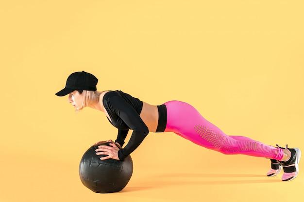 Kobieta w fitness ubrania trening z piłką lekarską. lekkoatletka robi trening brzucha za pomocą piłki medycyna.