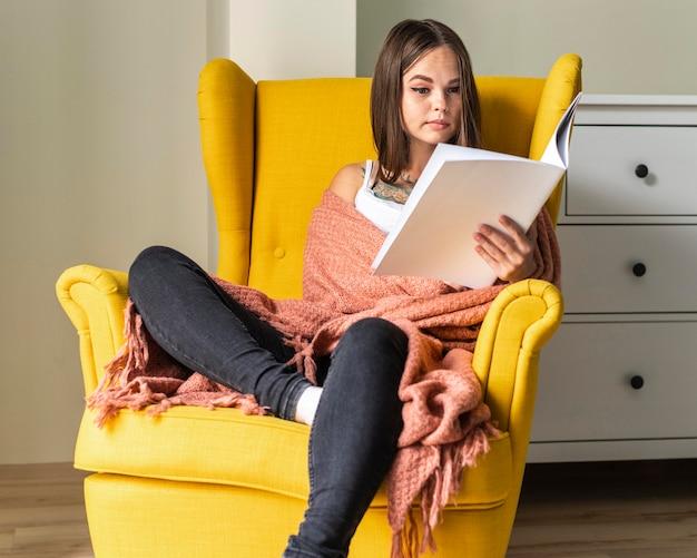 Kobieta w fotelu w domu, czytając książkę podczas pandemii