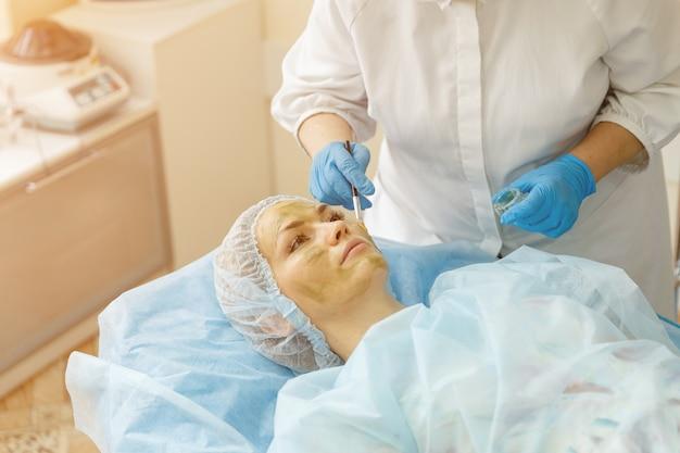 Kobieta w gabinecie kosmetologicznym podczas nakładania terapeutycznej maseczki przeciwstarzeniowej, światło słoneczne