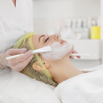 Kobieta w gabinecie kosmetycznym na zabieg na twarz