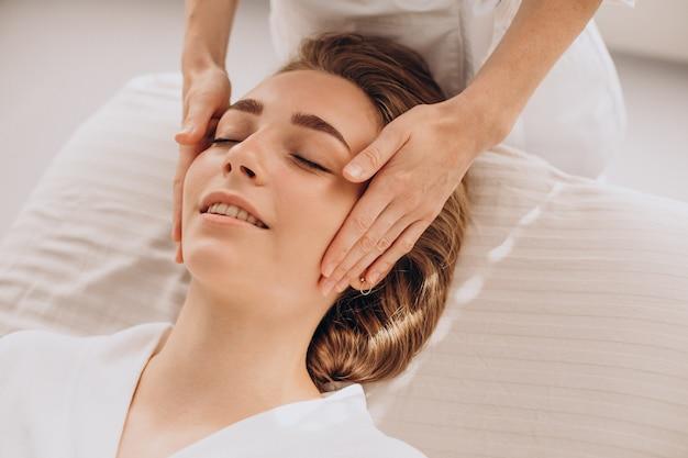 Kobieta w gabinecie kosmetycznym wykonująca masaż twarzy i szyi