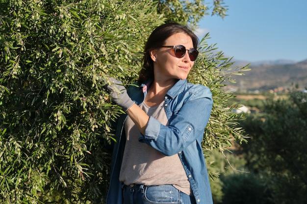 Kobieta w gaju oliwnym, niedojrzałe uprawy oliwek