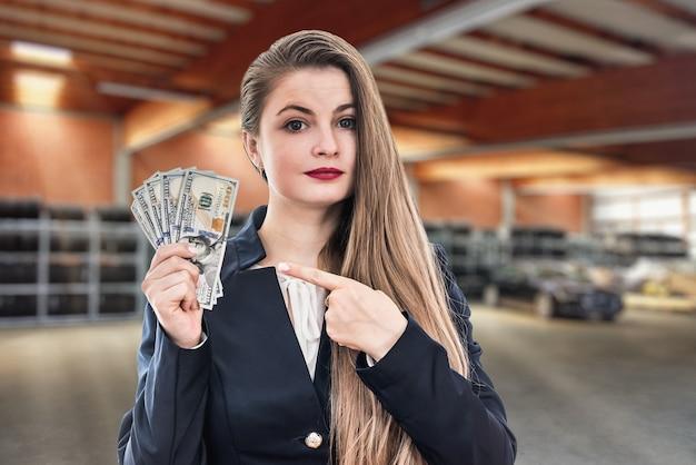 Kobieta w garażu na tle opon pokazuje dolara