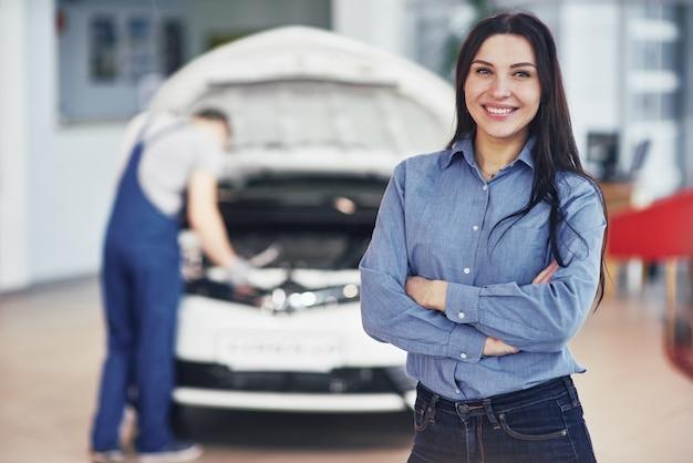 Kobieta w garażu samochodowym uzyskiwanie usługi mechaniczne. mechanik pracuje pod maską samochodu