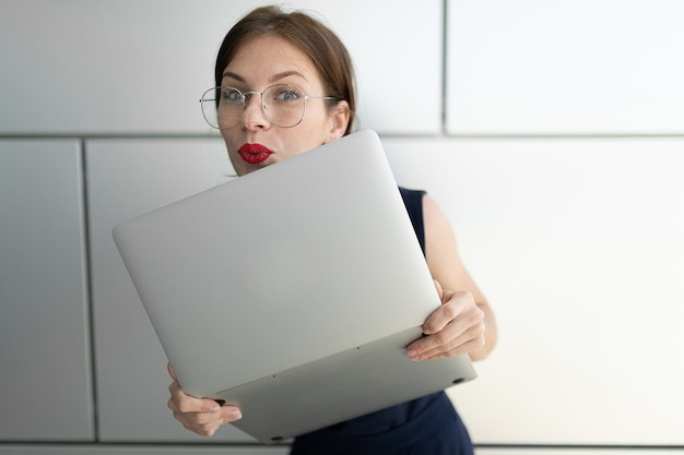 Kobieta w garniturze biurowym umówiła się na spotkanie i stała z laptopem na zewnątrz