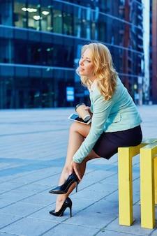 Kobieta w garniturze i butach siedzi na zewnątrz z telefonem i kawą na wynos