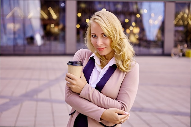 Kobieta w garniturze i filiżance kawy na wynos stoi w pobliżu centrum biznesowego