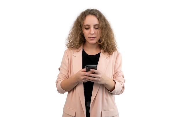 Kobieta w garniturze pisze z jej telefonu na białym tle