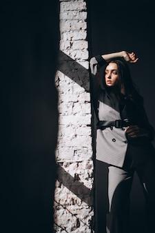 Kobieta w garniturze przy ścianie z cegły