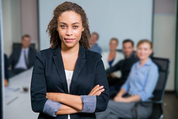 Kobieta w garniturze siedzi przy stole z partnerami za i rękami skrzyżowanymi