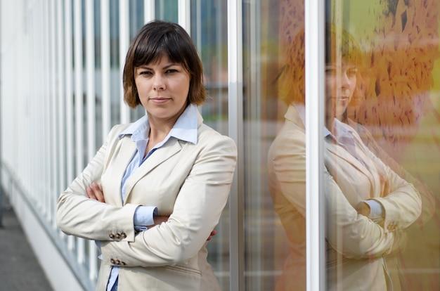 Kobieta w garniturze stojąc przed szklanym oknem ze skrzyżowanymi rękami