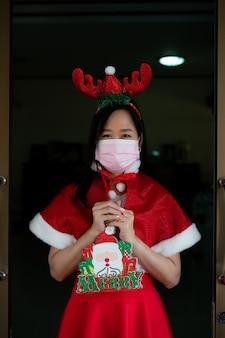 Kobieta w garniturze świętego mikołaja z noszeniem maski w boże narodzenie