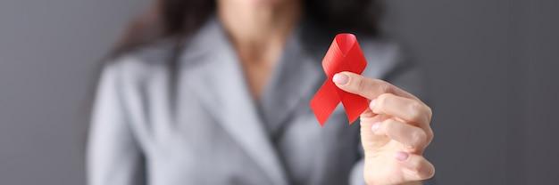 Kobieta w garniturze trzyma czerwoną wstążkę w dłoniach zbliżenie świat pomaga koncepcja dnia day