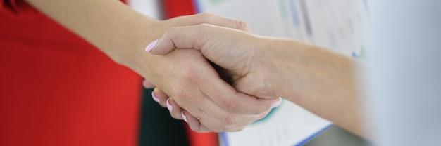 Kobieta w garniturze z dokumentami w ręku ściska ręce z inną kobietą. zawieranie umów o współpracę w koncepcji sfery biznesowej.