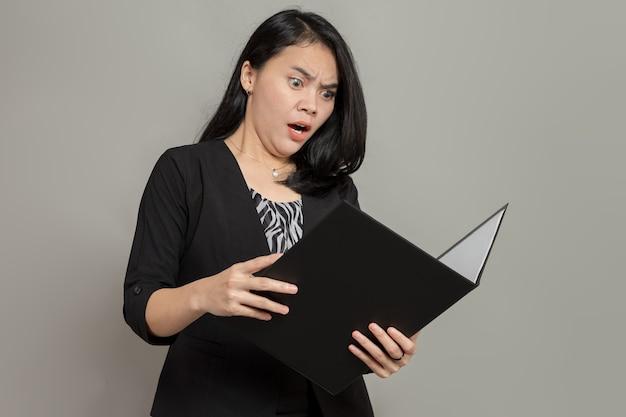 Kobieta w garniturze z gniewnym, zszokowanym wyrazem twarzy, trzymając i patrząc na folder