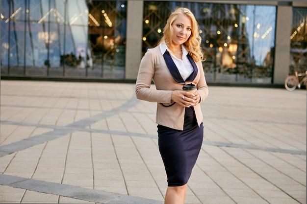 Kobieta w garniturze z kawą na wynos stoi w pobliżu centrum biznesowego