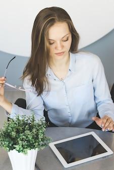 Kobieta w garniturze z komputerem typu tablet, makieta nad głową. pracownik biurowy, student