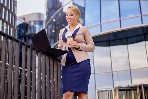 Kobieta w garniturze z laptopem i kawą w pobliżu biurowca