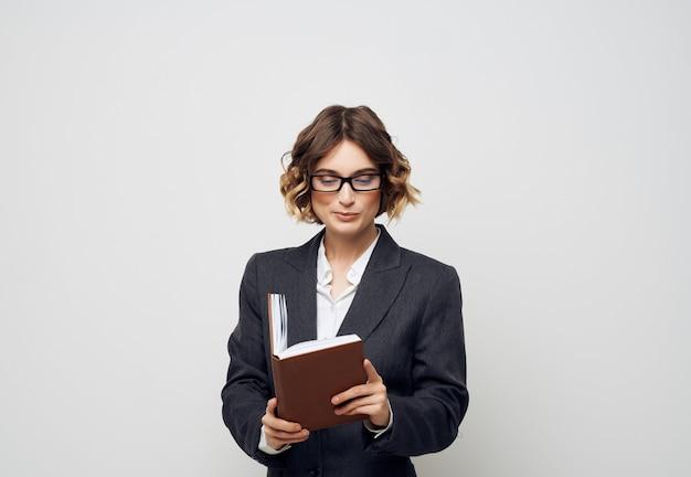 Kobieta w garniturze zeszyt w dłoni jasnym tle