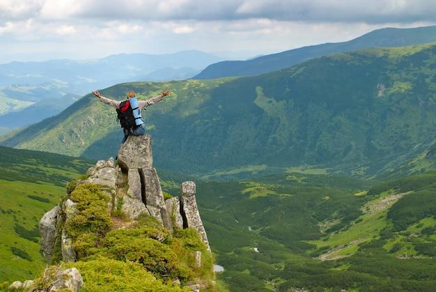 Kobieta w górach na skale z plecakiem z rozłożonymi rękami i mówi: kocham ten świat
