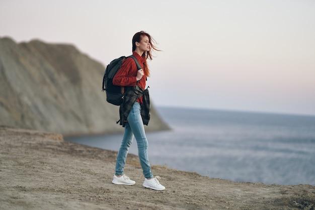 Kobieta w górach na świeżym powietrzu, w pobliżu morza na plaży z plecakiem na plecach