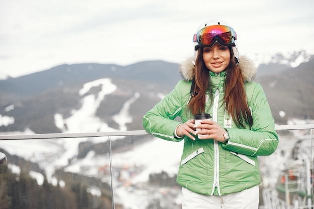 Kobieta w górach na zimowy dzień. pani w mundurze narciarskim.