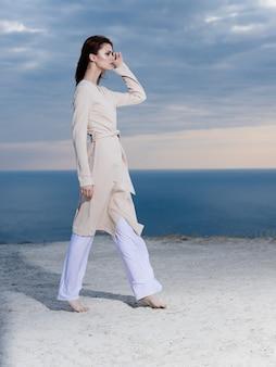 Kobieta w górach w pobliżu morza w przyrodzie i błękitne niebo