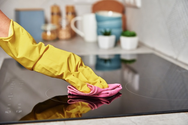 Kobieta w gumowych rękawiczkach czyści kuchenkę indukcyjną
