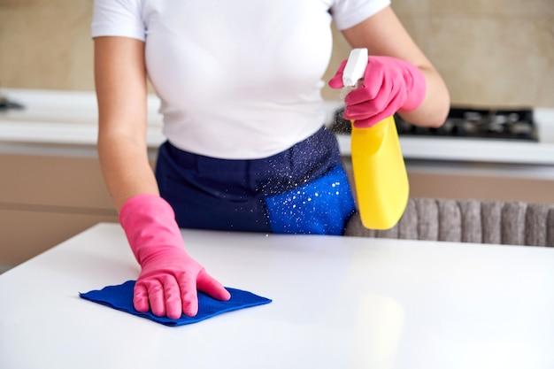 Kobieta w gumowych rękawiczkach do czyszczenia stołu szmatką dezynfekcja stołu kuchennego wybielaczem