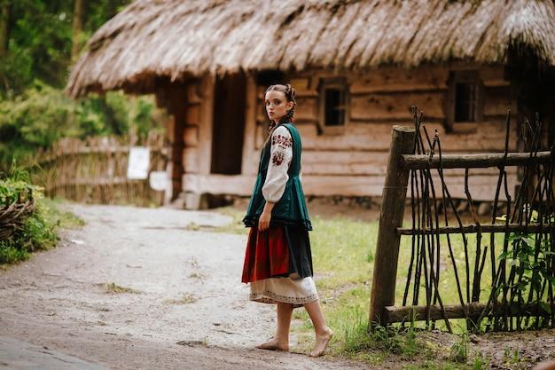 Kobieta w haftowanej sukni idącej po podwórku