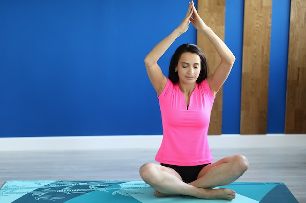 Kobieta w hali siedzi w pozycji lotosu z rękami do góry.