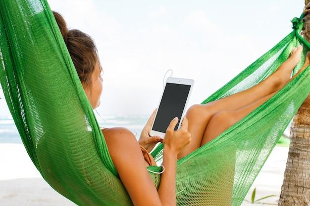 Kobieta w hamaku na plaży i przy użyciu komputera typu tablet
