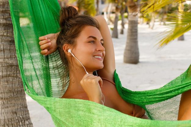 Kobieta w hamaku na plaży słucha muzyki lub książki audio