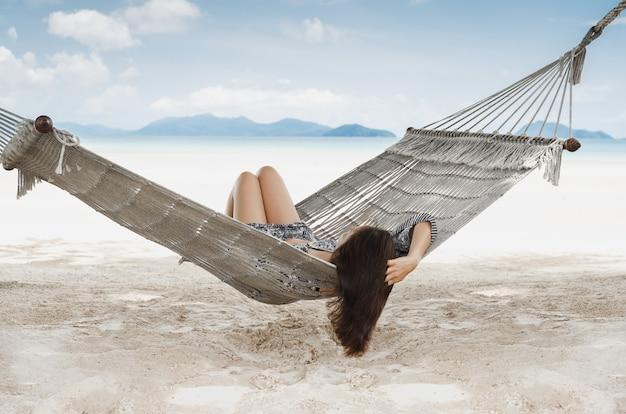 Kobieta w hamaku na tropikalnej plaży w letnie wakacje.