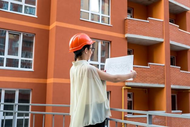 Kobieta w hełmie porównując plan i zbudowany budynek