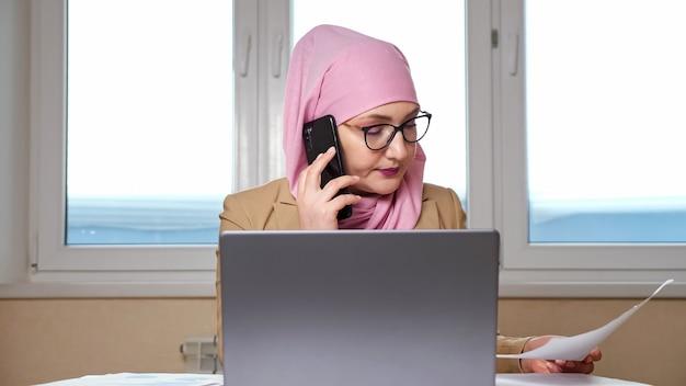Kobieta w hidżabie analizuje dokumenty i pracuje na laptopie podczas rozmowy przez telefon.